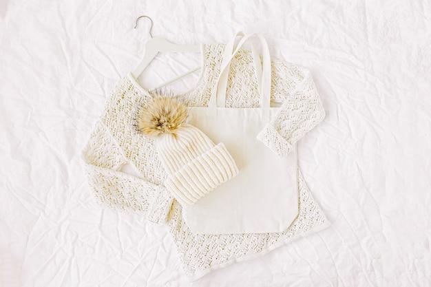 Gebreide witte trui met muts en draagtas. herfst/winter mode kleding collage op witte achtergrond. bovenaanzicht plat lag.