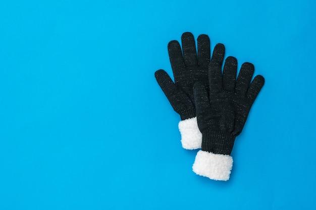 Gebreide zwarte dameshandschoenen op een donkerblauwe ondergrond. het concept van hoop en ontmoeting. mode accessoires voor dames.