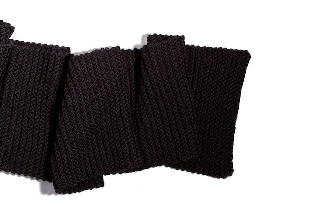Gebreide zwarte sjaal die op witte achtergrond wordt geïsoleerd
