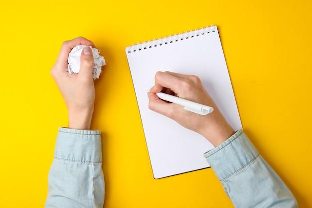 Gebrek aan ideeën. vrouwelijke handen schrijven in een notitieboekje en houden een verfrommelde bal papier op geel.