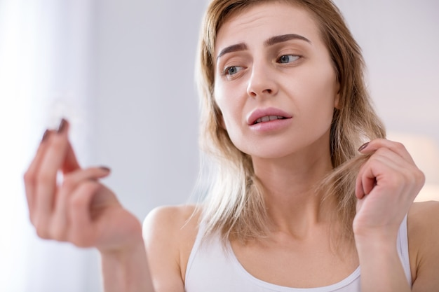 Gebrek aan vitamines. plukje haar in de handen van een ongezellige vrouw met ondergewicht terwijl ze ernaar keek