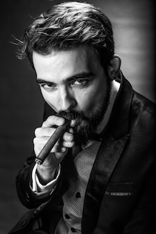 Gebrek en wit portret van bebaarde rokende man in een pak Premium Foto