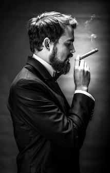 Gebrek en wit portret van bebaarde rokende man in een pak