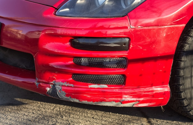 Gebroken autobumper van rode sportwagen met verlaagde ophanging