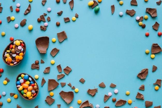 Gebroken chocolade-eieren en kleurrijke pellets