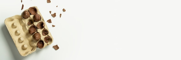 Gebroken chocolade paaseieren in een bakje en veelkleurige decoraties op een licht
