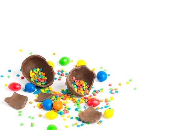 Gebroken chocoladepaasei en multicolored snoepjes op een wit. paasviering concept.
