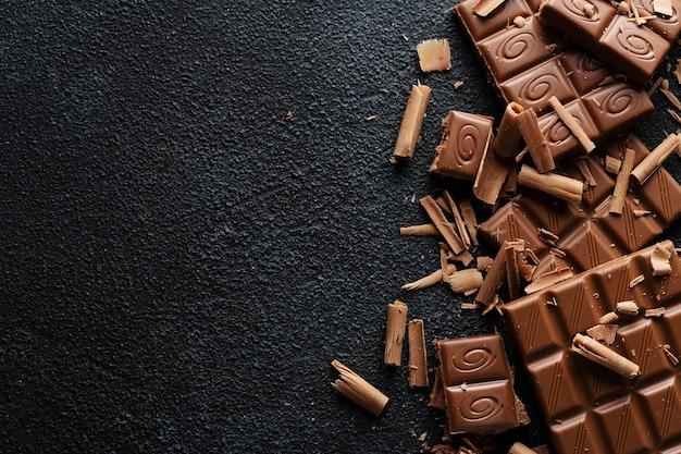 Gebroken chocoladerepen op donkere ondergrond