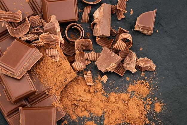 Gebroken chocoladestukjes en cacaopoeder op donker.