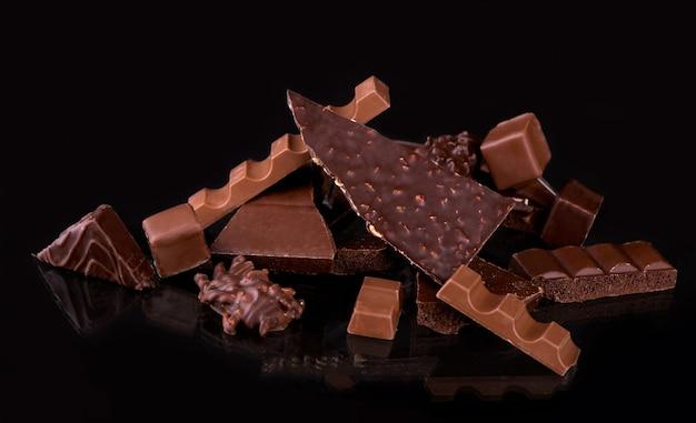 Gebroken chocoladestukjes en cacaopoeder op zwart