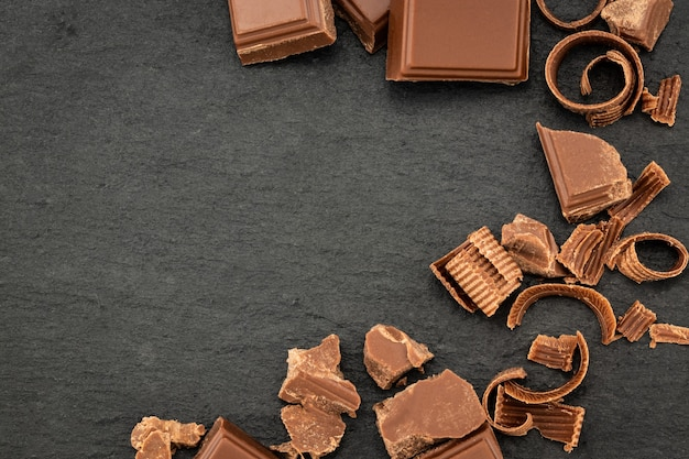 Gebroken chocoladestukjes en chocoladeschaafsel op een donkere