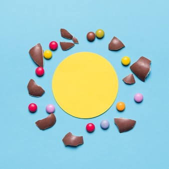 Gebroken die paaseishell en gemmen met leeg geel cirkelkader tegen blauwe achtergrond worden omringd
