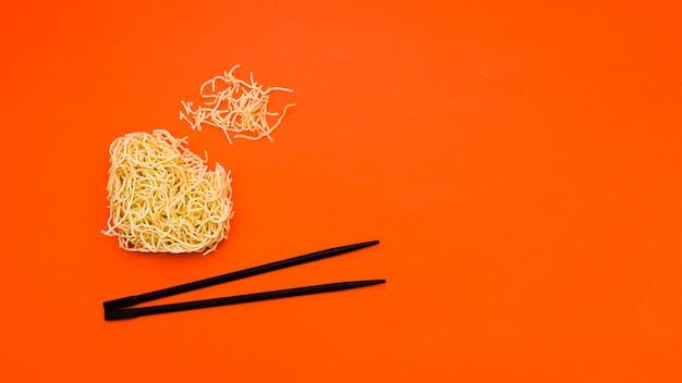 Gebroken droge onmiddellijke noedels met eetstokjes over oranje achtergrond
