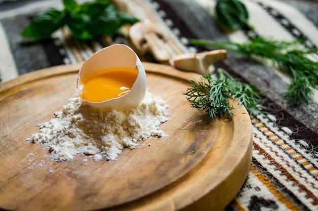 Gebroken ei in bloem op ronde snijplank, op donkere houten tafel met servet