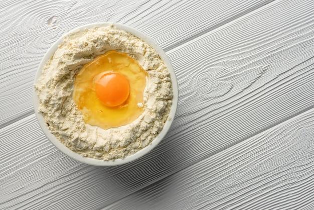Gebroken ei in een kom met bloem op een houten tafel