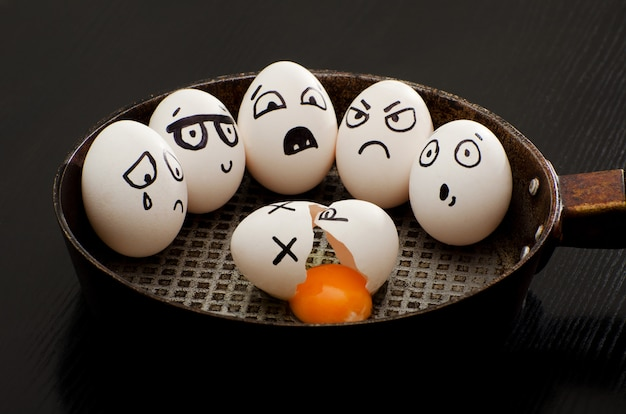 Gebroken ei in een pan omringd door hele eieren met verschillende emoties