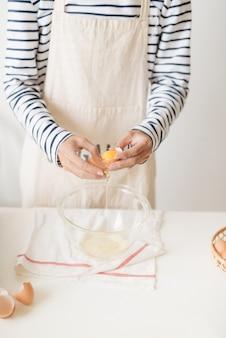 Gebroken ei in handen met gescheiden dooier