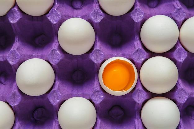 Gebroken ei onder hele in pakket. concept van uniciteit