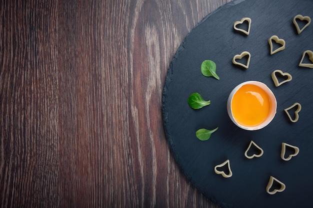 Gebroken ei op een zwarte ronde steen met een pasta van harten en bladgroente