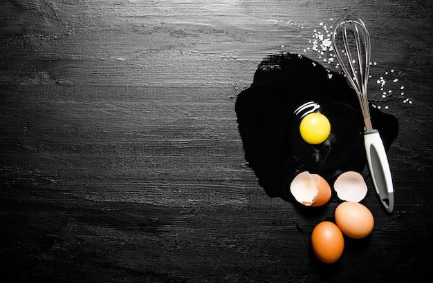 Gebroken eieren met een garde. op een zwarte houten tafel. vrije ruimte voor tekst. bovenaanzicht