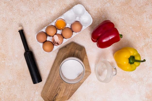 Gebroken eierschalen; olie fles; suikerkruik en groene paprika's op geweven achtergrond