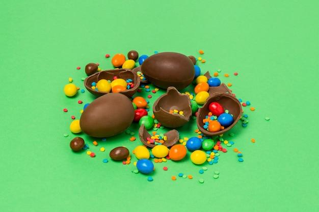 Gebroken en hele chocolade paaseieren, veelkleurige snoepjes, groene achtergrond. struik. concept van het vieren van pasen, pasen-decoraties. plat lag, bovenaanzicht. kopieer ruimte. gelukkig pasen.