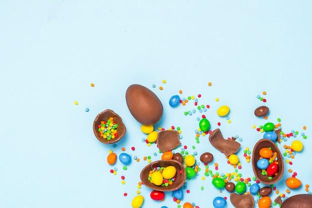 Gebroken en hele chocolade paaseieren, veelkleurige snoepjes op blauwe achtergrond. concept het vieren van pasen, pasen-decoraties, zoek naar snoepjes voor paashaas. plat lag, bovenaanzicht. kopieer ruimte.