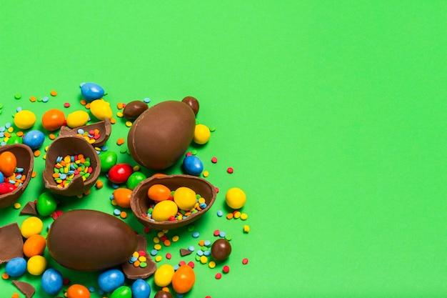 Gebroken en hele chocolade paaseieren, veelkleurige snoepjes op een groene achtergrond. struik. concept van het vieren van pasen, pasen-decoraties. plat lag, bovenaanzicht. kopieer ruimte.
