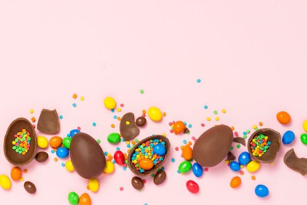 Gebroken en hele chocolade paaseieren, veelkleurige snoepjes op roze achtergrond. concept van het vieren van pasen, pasen-decoraties.