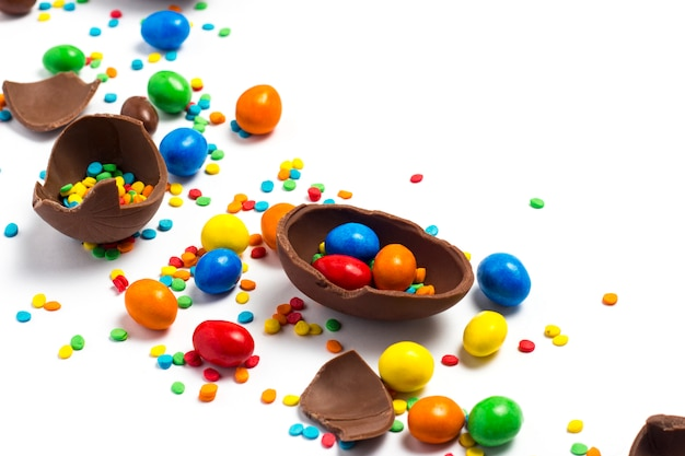 Gebroken en hele chocolade paaseieren, veelkleurige snoepjes op wit. concept het vieren van pasen, pasen-decoraties, zoek naar snoepjes voor paashaas. plat lag, bovenaanzicht. kopieer ruimte.