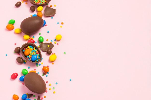 Gebroken en hele chocolade paaseieren, veelkleurige snoepjes, roze achtergrond. struik. concept van het vieren van pasen, pasen-decoraties. plat lag, bovenaanzicht. kopieer ruimte. gelukkig pasen.