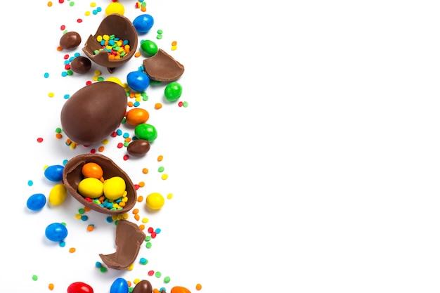 Gebroken en hele chocoladepaaseieren, veelkleurige snoepjes op witte achtergrond. concept het vieren van pasen, pasen-decoraties, zoek naar snoepjes voor paashaas. plat lag, bovenaanzicht. kopieer ruimte.