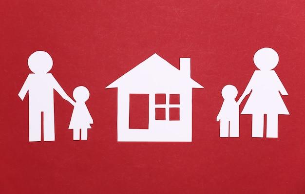 Gebroken gezin, scheiding. afdeling onroerend goed. gespleten papierfamilie, huis op een rood