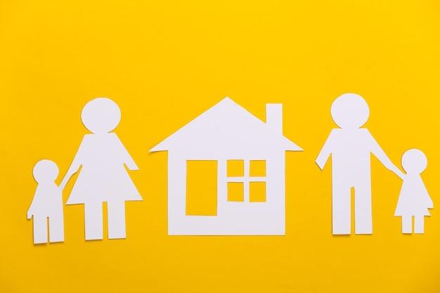 Gebroken gezin, scheiding. afdeling onroerend goed. gespleten papierfamilie, huis op geel