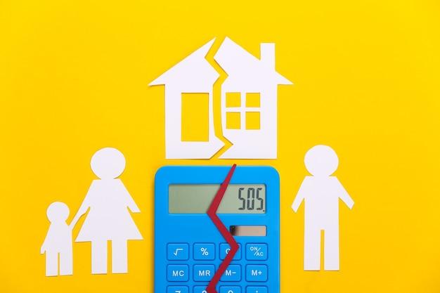 Gebroken gezin, scheiding. eigenschap divisie concept. gesplitste papierfamilie, rekenmachine en huis op geel
