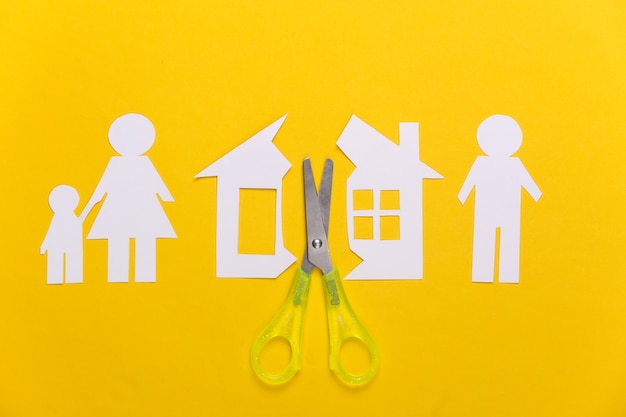 Gebroken gezin, scheiding. eigenschap divisie concept. schaar gesneden papieren huis, familie op geel