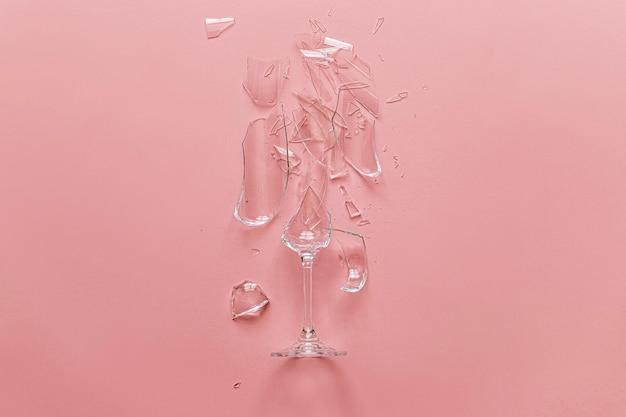 Gebroken glas op een roze achtergrond. gebroken liefde.