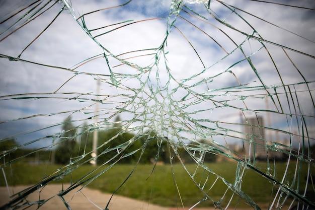 Gebroken glas op straat tegen de achtergrond van de stad