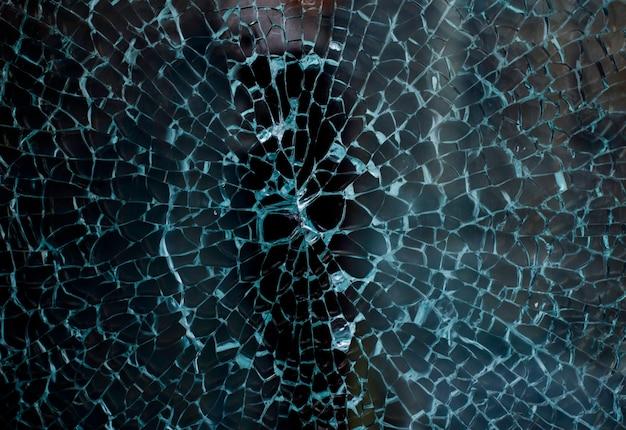Gebroken glas van een etalage van een kledingwinkel met ongericht achtergrond