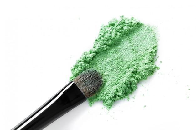 Gebroken groene oogschaduw en make-upborstel die op witte achtergrond wordt geïsoleerd