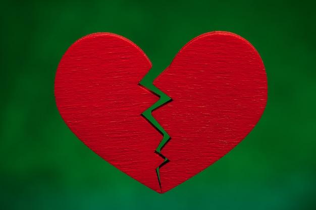 Gebroken hart. barst in het rode hart, de relatie verbreken. groene achtergrond.