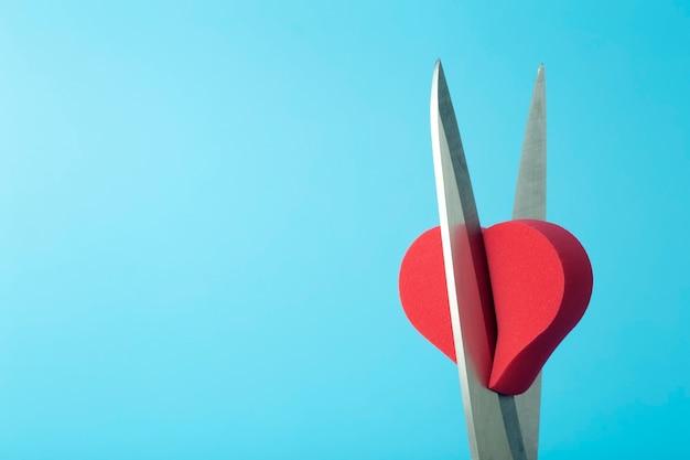 Gebroken hart dat met een schaar op een gekleurde achtergrond wordt gesneden. ongelukkige liefde