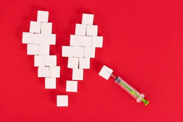Gebroken hart gemaakt van suikerklontjes en een spuit op een rode achtergrond. diabetesconcept. uitzicht van boven. creëer ruimte.