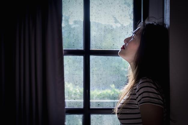 Gebroken hart jonge vrouw huilt in een donkere kamer met regenseizoen.