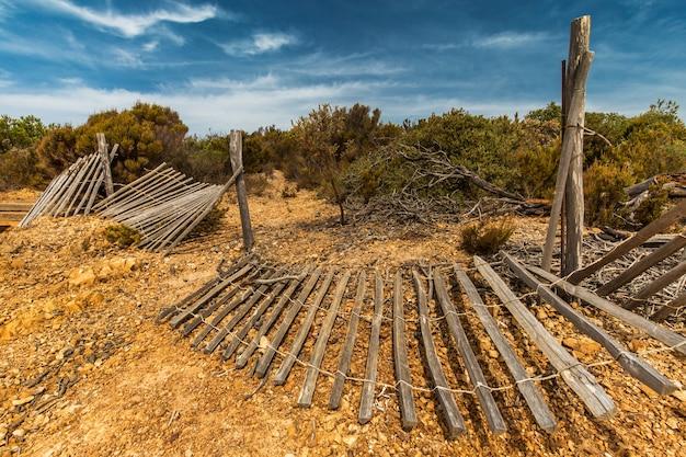 Gebroken hekken op de grond omgeven door groen onder het zonlicht en een blauwe lucht