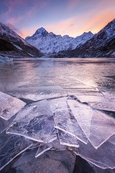 Gebroken ijs aan de oever van hooker lake onder south face van aoraki mount cook