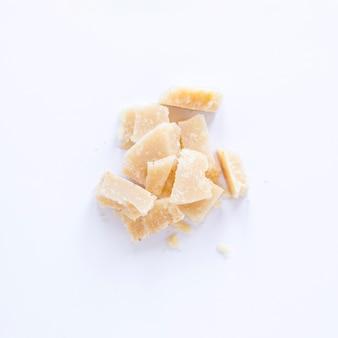Gebroken kaas die op witte achtergrond wordt geïsoleerd