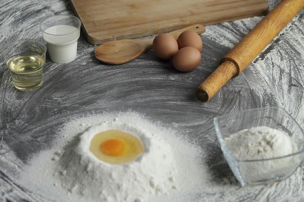 Gebroken kippenei in een stapel van bloem, olijfolie, melk, keukengereedschap op grijze tabelachtergrond.