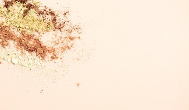 Gebroken kleurrijke oogschaduwen maken omhoog palet op pastelkleur oranje achtergrond.