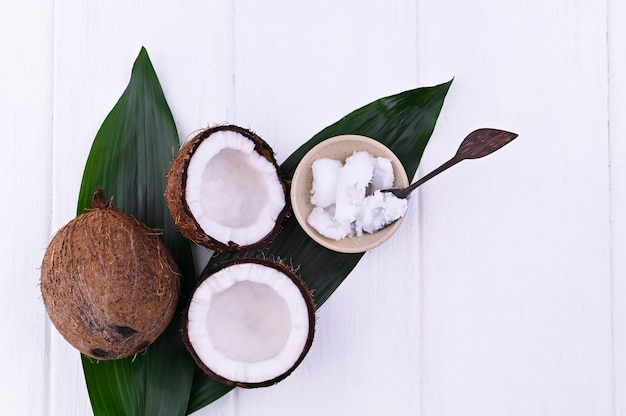Gebroken kokos en boter. exotisch fruit op een witte achtergrond. vrije ruimte voor tekst. kopieer ruimte. plat liggen.